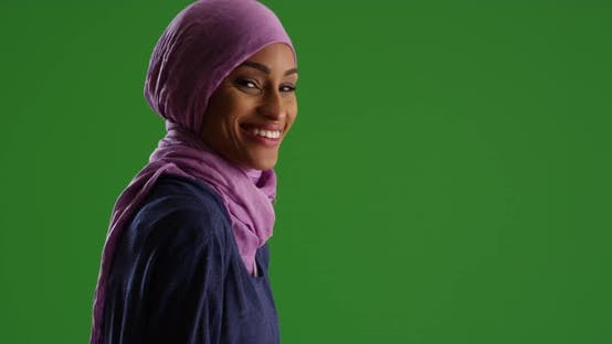 Thumbnail for Young black woman in purple headscarf, smiling at camera on green screen