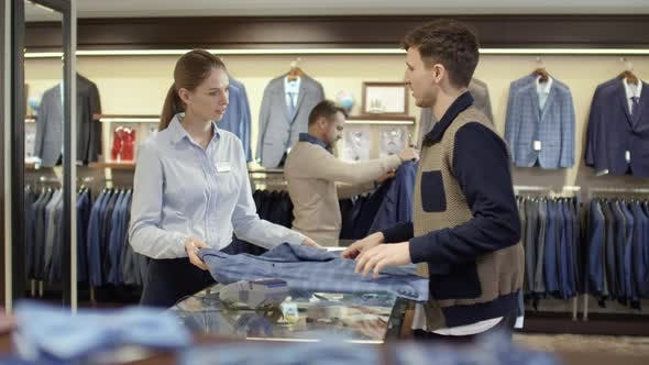 Thumbnail for Female Cashier Assisting Man Choosing Suit