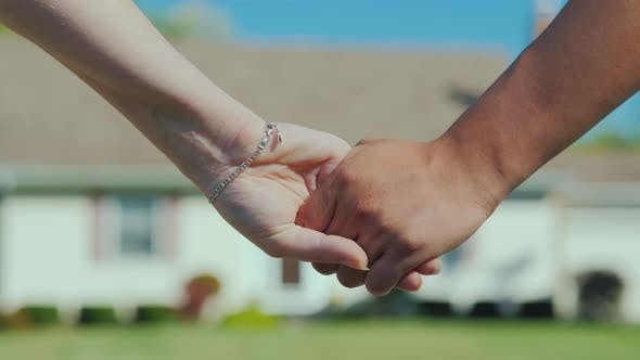 Cover Image for A Young Couple Holding Hands Against the Backdrop of Their New Home. Buying Real Estate Concept, a