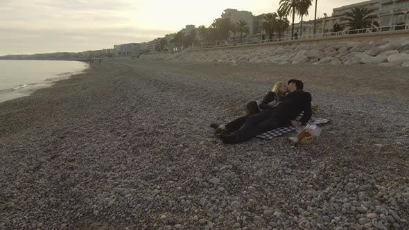 Cover Image for Male and female lying on blanket by seaside in Nice, kissing, romantic evening