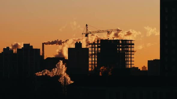Thumbnail for Silhouette of Crane Workers Working on Construction Site Residential Building Sunrise or Sunset