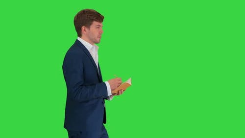 Thinking Businessman Writing Notes in His Notebook While Walking on a Green Screen, Chroma Key.