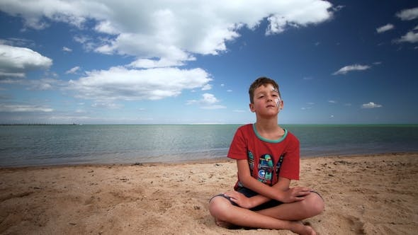 Thumbnail for Little Boy Is Sitting on the Beach