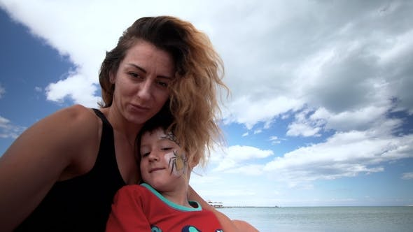 Thumbnail for Child and Mom on a Beach Are Played, Embrace and Kiss. Selfie