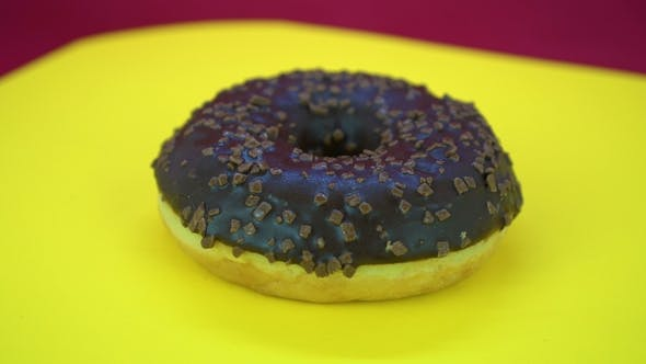 Cover Image for Delicious Sweet Donut Rotating on a Plate. Top View. Bright and Colorful Sprinkled Donut