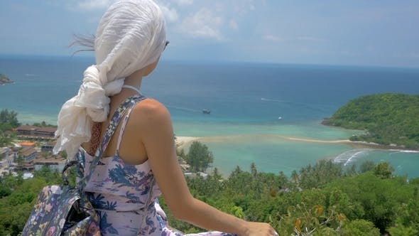 Thumbnail for Young Tourist Woman Is Sitting at Viewpoint of Beautiful Sea Bay Landscape