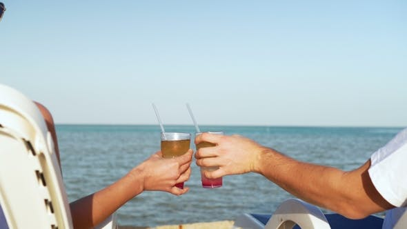 Thumbnail for Young Family Couple Sunbathing and Drinking Colored Cocktail at Tropical Beach. Lovers on Honeymoon