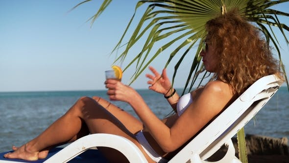 Thumbnail for Young Girl in Bikini on Beach with Party Cocktail
