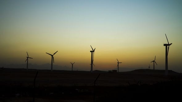 Cover Image for Beautiful Windmill Turbines Harnessing Clean, Green, Wind Energy Silhouetted in the Sunset Sky with