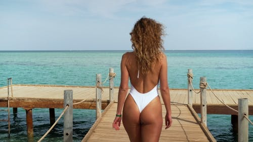 Girl in Swimwear Walking on the Pier. Sea and Sky in the Background