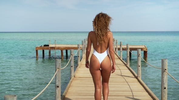 Thumbnail for Girl in Swimwear Walking on the Pier. Sea and Sky in the Background