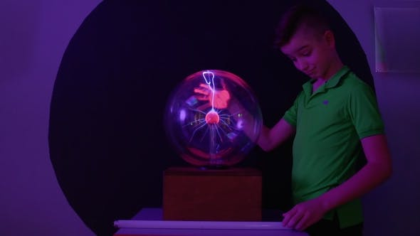 Thumbnail for Boy Conducts Electricity and Lights the Lamp Using His Body and Plasma Globe