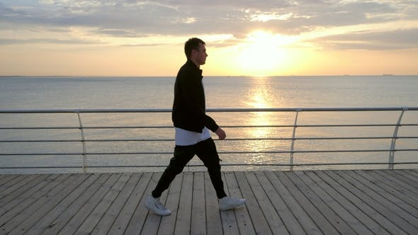 Cover Image for Silhouette of Young Trendy Modern Man Walking Along Wooden Embankment Near Sea or Ocean. Man in