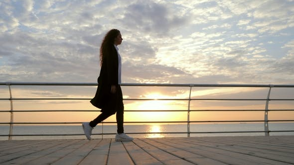 Thumbnail for Silhouette of Young Stylish Business Woman with Curly Hair Are Walking Along the Wooden Embankment
