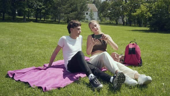 Young Couple Taking Selfie with Mobile Phone in the Park