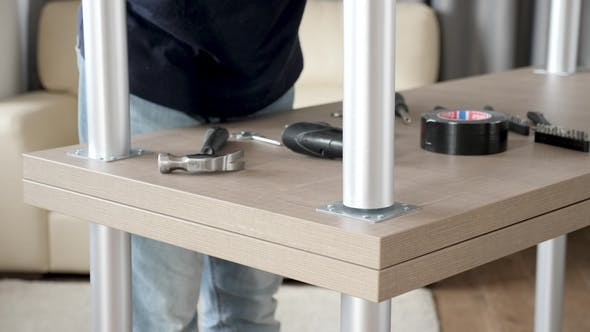 Thumbnail for Man Approaching a Turned Table and Unscrews a Leg