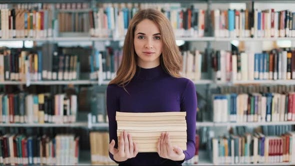 Thumbnail for Smiling Female Student Hold Books Standing Before the Shelves in the Library