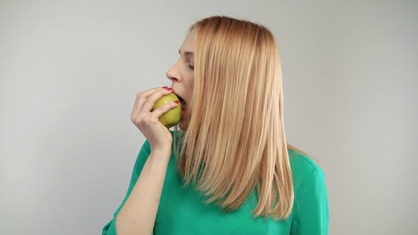 Thumbnail for Portrait of Blonde Woman Eating Green Apple. Young Woman Propose To Bite Apple
