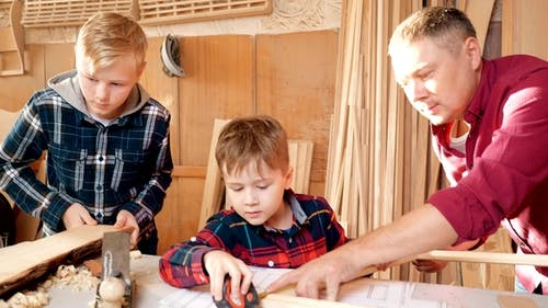 Family, Carpentry, Woodwork and People Concept. Father Teaches Son Carpentry