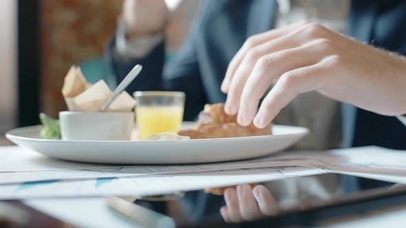 Thumbnail for Young Successful Businessman Is Eating Delicious Lunch, Sitting at Table in Restaurant, Business