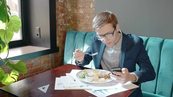 Thumbnail for Young Handsome Guy Is at Business Lunch, Using Smartphone, Sitting at Table in Cafe, Eating Tasty