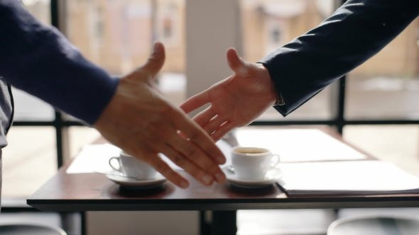 Cover Image for Two Businessman Shaking Hands in Cafe After Negotiations