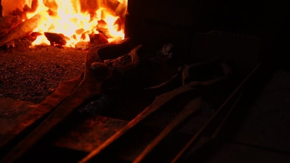 Thumbnail for Blacksmith Fanning the Flames of the Furnace Using the Tools Prevents Embers