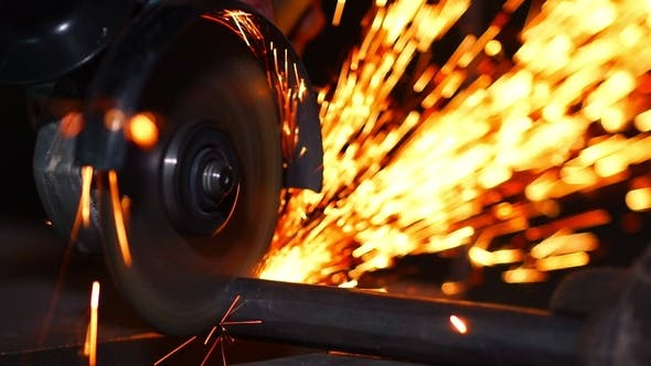 Man Working with Grinder while Sparks Fly