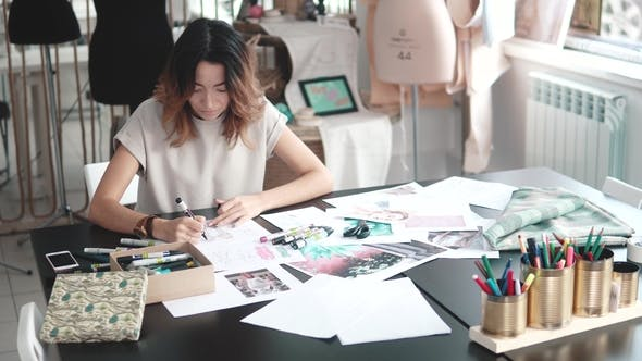 Thumbnail for Designer of Clothes Makes a Sketch of Clothes in a Sewing Workshop. a Girl Working for Herself Is