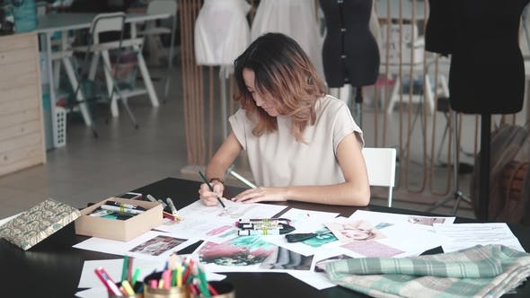Thumbnail for Young Fashion Designer Girl Makes a Sketch in Pencil at the Atelier. Business Woman with Asian