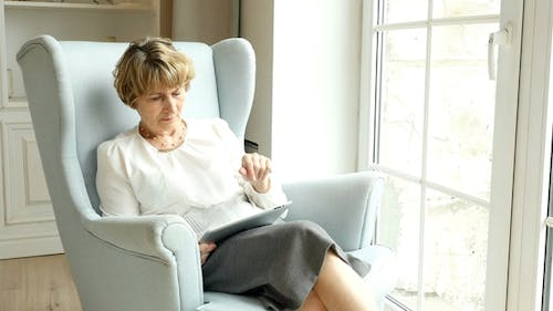 Senior Attractive Woman Sits And Websurfing On Internet With Tablet Computer