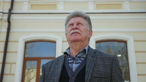 Respected Old Man in a Business Suit Stands at a House in Spring in