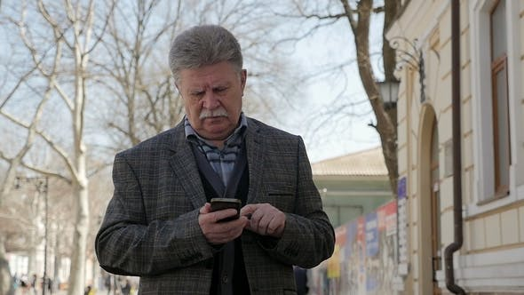 Cover Image for Grey-Headed Man with Mustache Walks and Browses the Net on a Phone in Spring