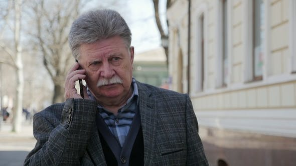 Thumbnail for Elderly Man with Mustache Goes and Talks on His Phone in Spring in