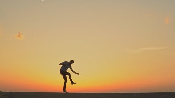 A Man Is Dancing at Sunset