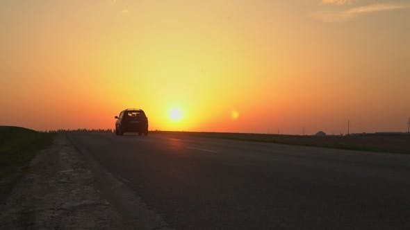 Thumbnail for The Car Is Driving Along the Road Against the Sunset