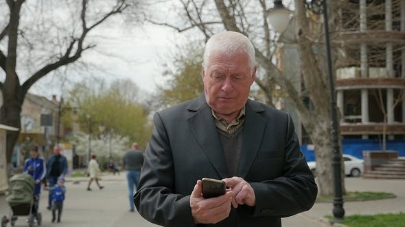 Thumbnail for Elderly Man Goes Along a City and Touches His Mobile in Spring in