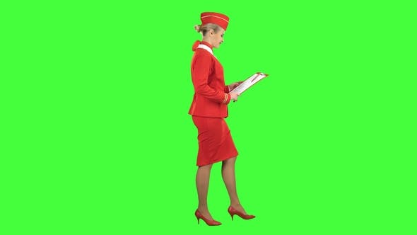 Thumbnail for Woman Steps Along with a Red Folder in Her Hands. Green Screen. Side View