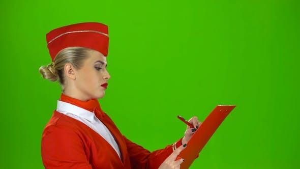 Thumbnail for Girl Writes a Pen in a Special Folder, She Is a Flight Attendant. Green Screen. Side View