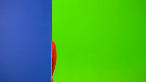 Thumbnail for Girl Peeks Out From Behind a Blue Board and Shows a Thumbs-up. Green Screen