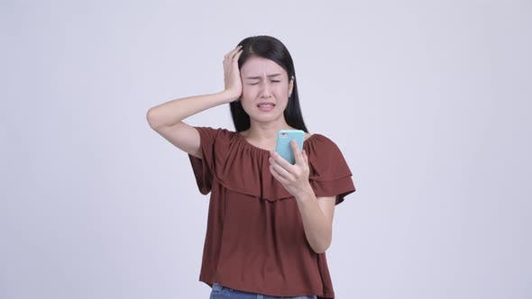 Cover Image for Stressed Asian Woman Using Phone and Getting Bad News