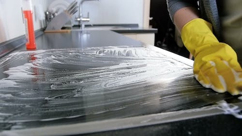 Video of Young Woman in Yellow Rubber Gloves Cleaning Electric Induction Stove with Deteregnt Suf
