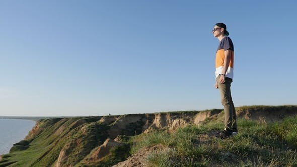 Thumbnail for Excited Young Man Stands on the Hilly Black Sea Coast in Summer in Slo-mo