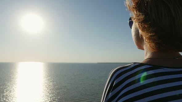Cover Image for Romantic Blond Woman Stands and Enjoys the Sunset on the Black Sea Coast