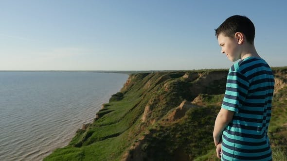 Thumbnail for Impressed Boy Looks at Calm Black Sea Waters in Summer