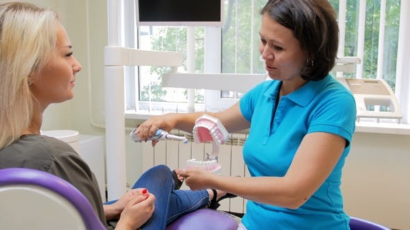 Thumbnail for Footage of Female Dentist Teaching Patient How To Clean Teeth with Electric Brush