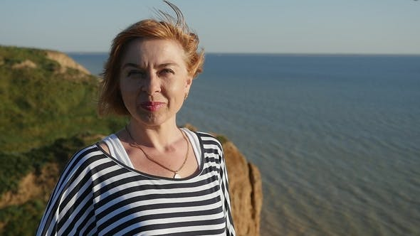 Cover Image for Happy Woman Stands on the Black Sea Coast and Smiles in Summer