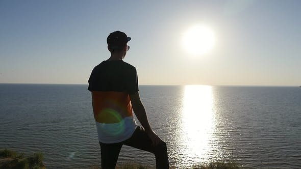 Thumbnail for Snappy Young Man Stands on the Black Sea Shore at Golden Sunset