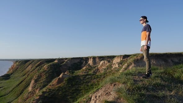 Thumbnail for Brave Young Man Stands on the Hilly Black Sea Shore in Summer in Slo-mo
