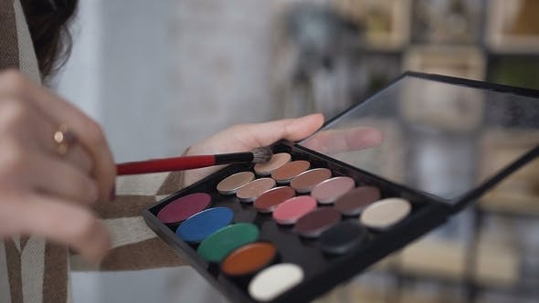 Thumbnail for . A Palette with Eye Shadows and a Makeup Brush in Makeup Artist's Hands. The Girl Holding
